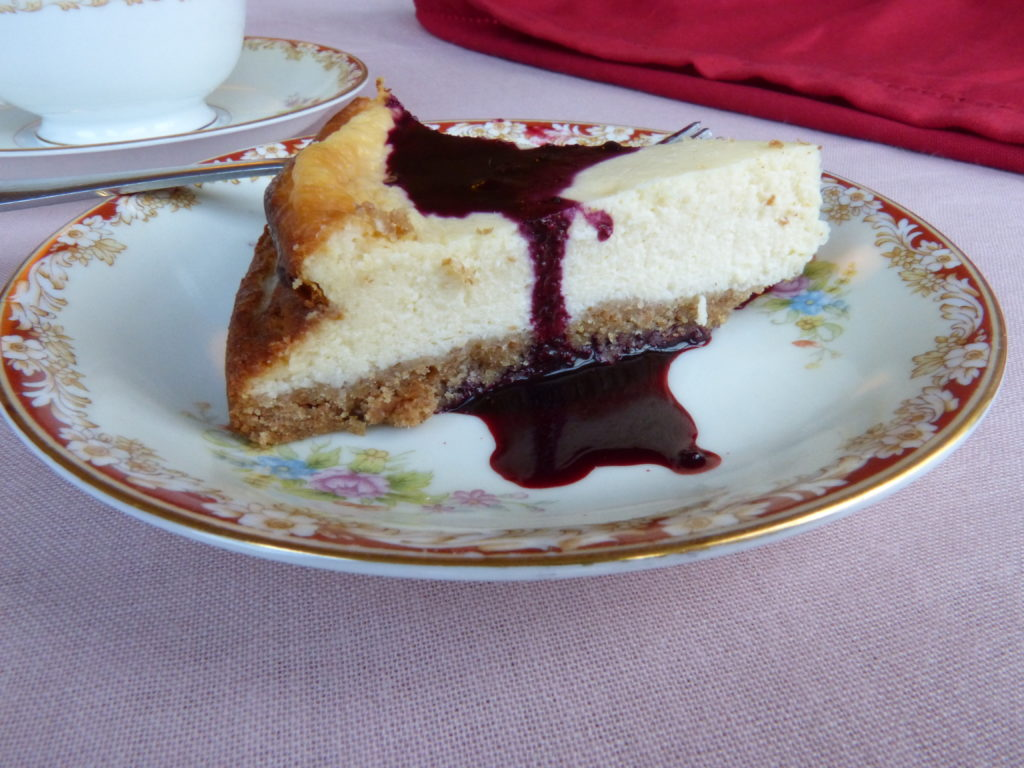A slice of cheese cake with blackberry coulis