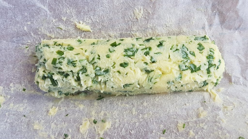 A roll of freshly made Spring wild herb butter