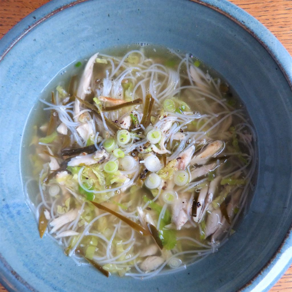Bowl of chicken broth with bladder wrack and noodles