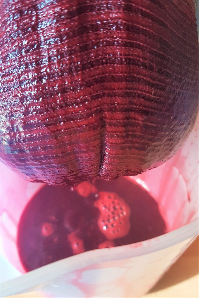 Straining blackberry syrup through a jelly bag