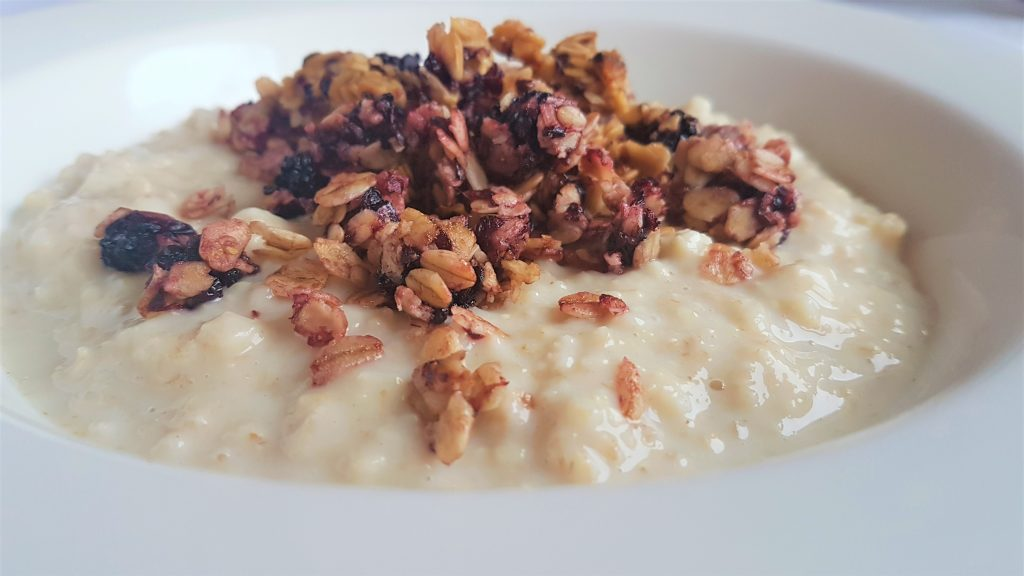 bowl of porridge with blackberry-seed granola on top