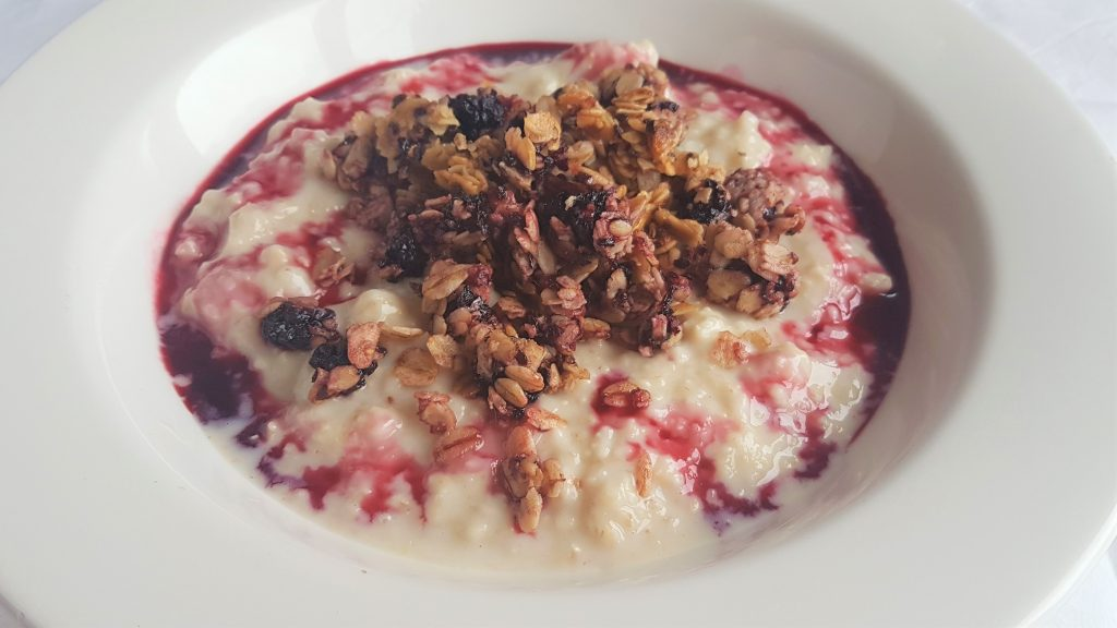 Bowl of porridge with blackberry-seed granola and blackberry cordial