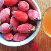 Bowl of rosehip fruits next to a glass of rosehip syrup