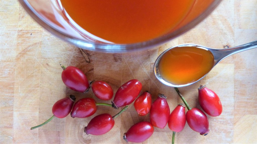 Rosehip syrup on a spoon and rosehips