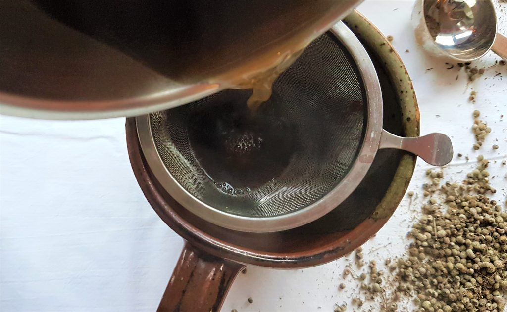 Straining cleaver seeds and spices through a strainer