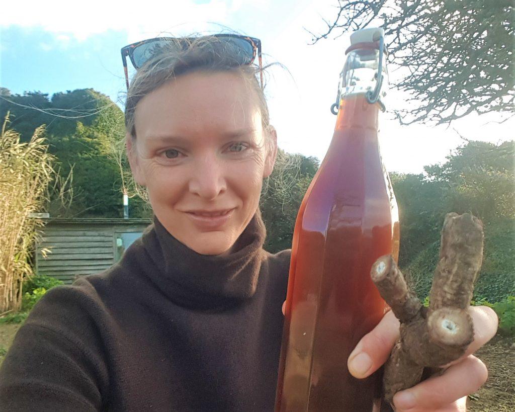Forager Rachel Lambert holding a bottle of homemade burdock beer