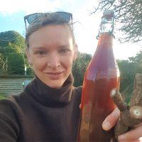 Foraging guide Rachel Lambert holding a bottle of homemade wild burdock beer